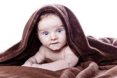 Bebé hermoso que miente en la toalla Imagen de archivo