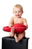Bebé hermoso que se sienta con la almohadilla en forma de corazón Fotos de archivo
