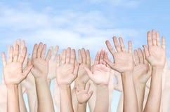 Bebê, homens e mulheres levantando as mãos contra Fotos de Stock