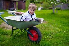 Bebé joven lindo dentro de la carretilla en jardín Fotografía de archivo