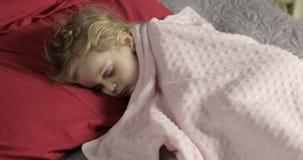 Beb? lindo que duerme en la cama en casa Ni?a que duerme en luz de la ma?ana imagen de archivo libre de regalías