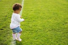 Bebé lindo que hace sus primeros pasos de progresión Imagen de archivo libre de regalías