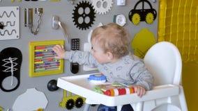 Beb? lindo que juega con el tablero ocupado en la pared Tablero de madera del juego almacen de video