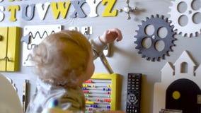 Beb? lindo que juega con el tablero ocupado en la pared Juguetes educativos Ocupado-tablero para los ni?os Tablero de madera del  almacen de video
