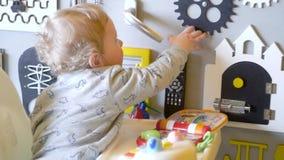 Beb? lindo que juega con el tablero ocupado en la pared Ocupado-tablero para los ni?os Tablero de madera del juego metrajes