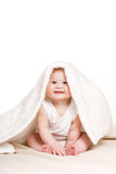 Bebé lindo que mira a escondidas hacia fuera de debajo la manta Foto de archivo libre de regalías
