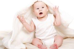 Bebé lindo que mira a escondidas hacia fuera de debajo la manta Fotos de archivo libres de regalías