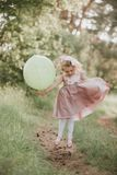 Beb? ? moda que guarda o bal?o grande que veste o vestido cor-de-rosa na moda no prado playful Festa de anos fotografia de stock