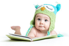 Bebê na coruja feita malha engraçada do chapéu com livro Imagem de Stock