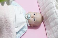 Bebê no berço com almofada e a chupeta abundantes Fotografia de Stock Royalty Free