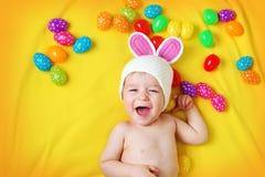 Bebê no chapéu do coelho que encontra-se na cobertura amarela com ovos da páscoa Imagens de Stock