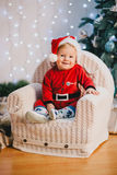 Bebê no terno de Santa Claus que senta-se sob a árvore de Natal Imagem de Stock Royalty Free