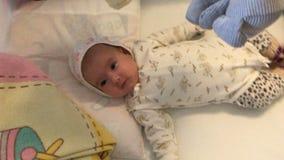 Bebê pequeno que encontra-se na cama e no close-up de sorriso vídeos de arquivo