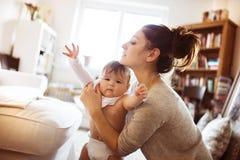Bebê pequeno que obtém vestido por sua mãe Imagem de Stock Royalty Free