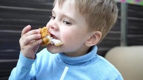 Beb? que come el pollo frito en un restaurante de los alimentos de preparaci?n r?pida, primer almacen de metraje de vídeo