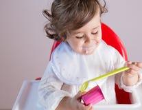 Bebé que come el yogur con la cara sucia Imagenes de archivo