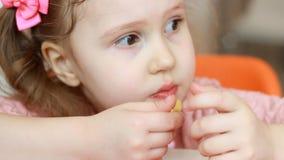 Beb? que come las patatas fritas de los alimentos de preparaci?n r?pida en un caf? Primer del retrato metrajes