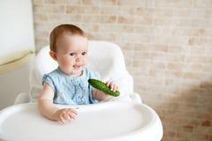 Beb? que come vegetais pepino verde na m?o da menina na cozinha ensolarada Nutri??o saud?vel para crian?as Petisco ou café da man fotografia de stock royalty free