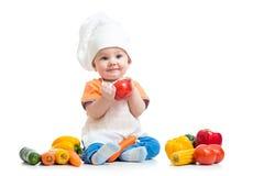 Bebê que desgasta um chapéu do cozinheiro chefe com vegetais Fotos de Stock Royalty Free