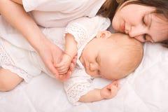 Bebé que duerme con la madre Foto de archivo