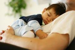 Bebé que duerme en el pecho del papá Fotografía de archivo libre de regalías