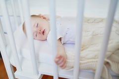 Beb? que duerme en el pesebre del co-durmiente atado a la cama de los padres imágenes de archivo libres de regalías