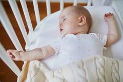 Beb? que duerme en el pesebre del co-durmiente atado a la cama de los padres foto de archivo libre de regalías