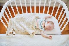 Beb? que duerme en el pesebre del co-durmiente atado a la cama de los padres imagen de archivo