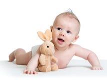 Bebê que encontra-se na barriga com brinquedo do coelho Fotos de Stock Royalty Free