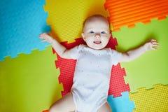 Beb? que encontra-se na esteira colorida do jogo no assoalho fotografia de stock royalty free