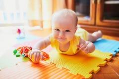 Beb? que encontra-se na esteira colorida do jogo no assoalho fotos de stock royalty free