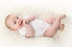 Bebê que encontra-se no sorriso traseiro Foto de Stock