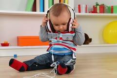 Bebê que escuta a música com auscultadores Fotografia de Stock Royalty Free