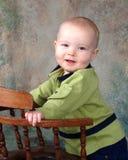 Bebê que está pela cadeira de madeira Fotos de Stock