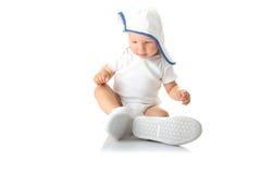 Bebé que intenta en los zapatos y el casquillo basebal Imagen de archivo