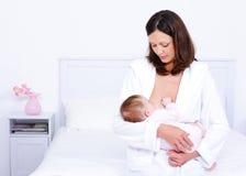 Bebé que introduce de la madre con el pecho Imagen de archivo
