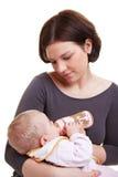 Bebé que introduce de la madre con leche Imagen de archivo