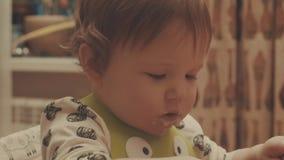 Bebê que joga com a colher e que come o papa de aveia filme