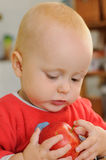 Bebé que juega con la manzana Fotos de archivo