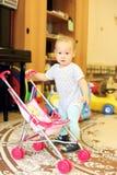 Bebé que juega con la muñeca Imagenes de archivo