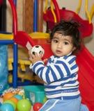 Bebé que juega con las bolas en un área de juego Imagen de archivo
