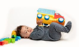 Beb? que juega con las unidades de creaci?n y el cami?n en el fondo blanco imagen de archivo libre de regalías