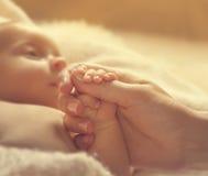 Bebé que lleva a cabo las manos de la madre, salud recién nacida enferma, ayuda recién nacida Foto de archivo libre de regalías