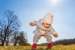 Beb? que lleva el sombrero caliente de la gorrita tejida, la camiseta y botas rojas al aire libre en la zona rural que descubre l imagen de archivo