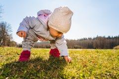 Beb? que lleva el sombrero caliente de la gorrita tejida, la camiseta y botas rojas al aire libre en la zona rural que descubre l fotos de archivo