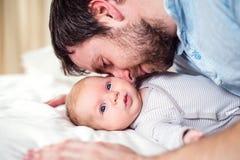 Bebé que miente en la cama, sostenida por su padre Foto de archivo