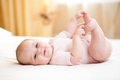 Bebé que miente en la hoja blanca y que lleva a cabo sus pies Fotografía de archivo libre de regalías