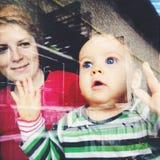 Bebé que mira a través de ventana Imagen de archivo