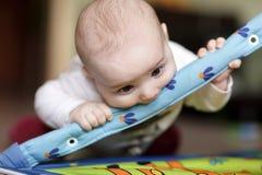 Bebé que muerde jugando la estera Imagenes de archivo