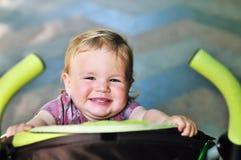 Bebé que se divierte en el cochecito Fotografía de archivo